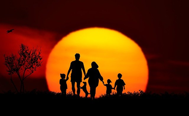 family with dog at sunset – 9 best small dog breeds for families
